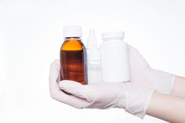 Halten sie kranke hilfe ohrhilfe komplexes einweg-label-logo kopieren-spave leeres paracetamol präsentieren promo krankenhaus klinik sirup husten konzept. die hände der person zeigen eine reihe von objekten, die auf weißem hintergrund isoliert sind