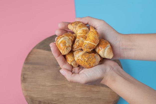 Halten sie mini-croissant-kekse in der hand.