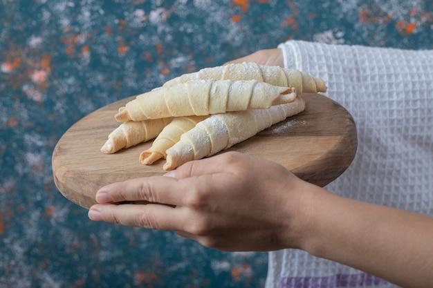 Halten sie mutaki kekse auf einem holzbrett in der hand.