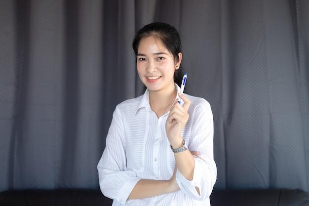 Haltener stift des asiatischen mädchens stehender und glücklich lächeln