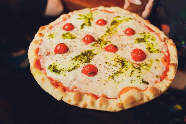 Halteplatte der jungen frau mit geschmackvoller pizza, abschluss herauf ansicht.