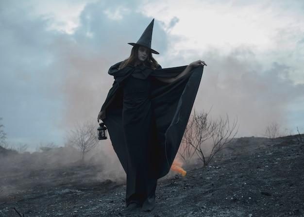 Haltung eines mannes im schwarzen hut und in der kleidung der hexe