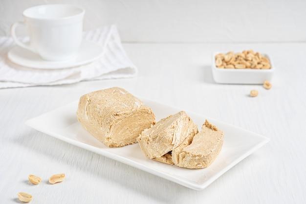 Halva, auch halvah, asiatisches hausgemachtes dessert aus öligen erdnusssamen auf teller auf holztisch