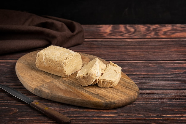 Halva, auch halvah, türkisches lokales dessert aus öligen samen oder nüssen, geschnitten auf schneidebrett
