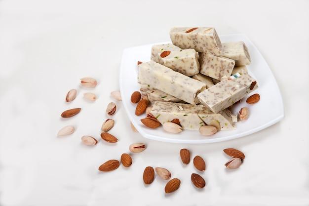 Halva aus sonnenblumenkernen, mandeln und pistazien liegt auf einem teller auf weißem grund. spas kopieren.