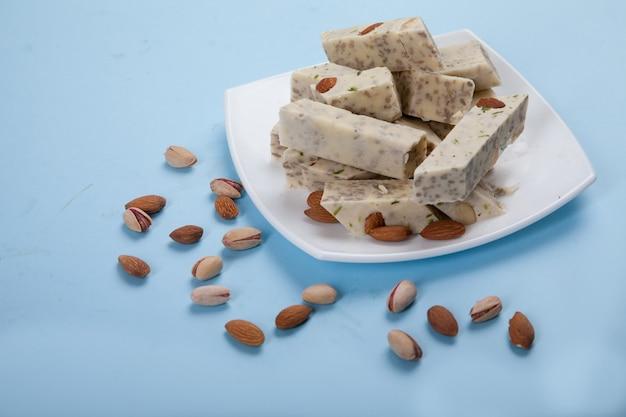 Halva aus sonnenblumenkernen, mandeln und pistazien liegt auf einem teller vor blauem hintergrund. pistazien und mandeln werden nebeneinander verstreut.