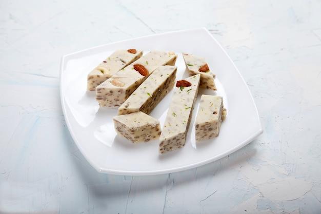 Halva mit pistazien und mandeln auf einem weißen porzellanteller auf weißem hintergrund.