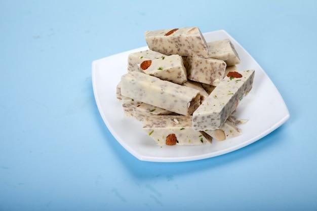 Halva mit pistazien und mandeln steht auf einem weißen porzellanteller vor blauem hintergrund.