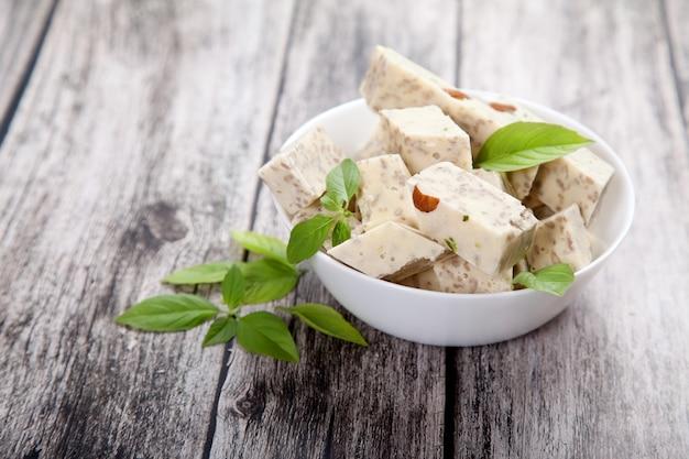 Halva mit pistazien und mandeln und grünen blättern in einer porzellanschale auf holzhintergrund.