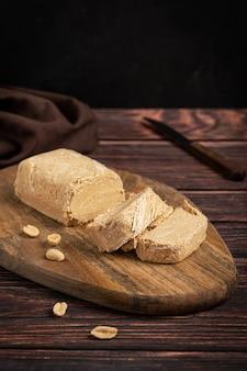 Halva oder halvah westasien süßes dessert aus öligen erdnusssamen, serviert auf holzschneidebrett