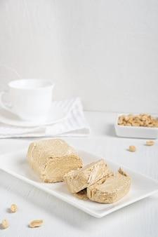 Halva oder halwa östliches dessert aus öligen erdnusssamen auf weißem teller auf holztisch mit handtuch