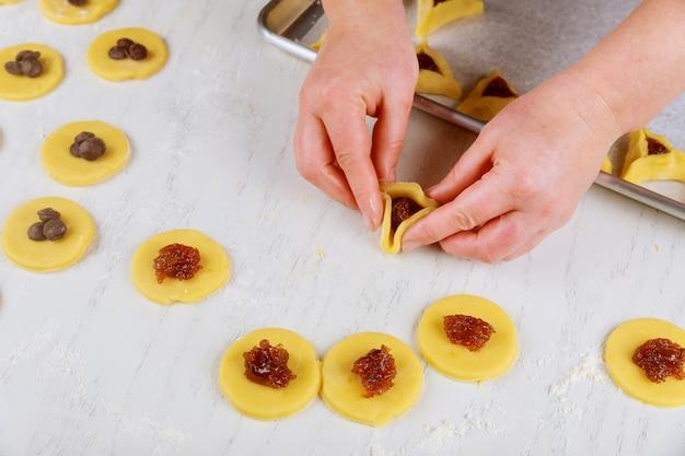 Hamantaschen-kekse für purim vorbereiten. jüdisches feiertagskonzept,