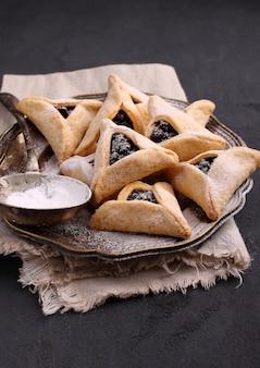 Hamantaschenplätzchen mit mohn und risinen und puderzucker auf einer platte, gekocht für jüdisches fest von purim.