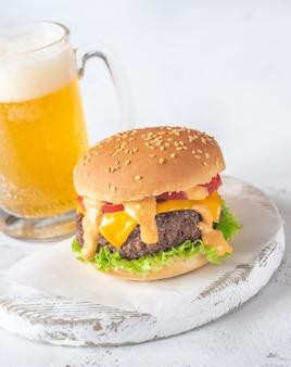 Hamburger auf dem holzbrett mit einem becher bier