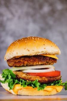 Hamburger mit doppeltem fleisch, tomate, käse, zwiebel.