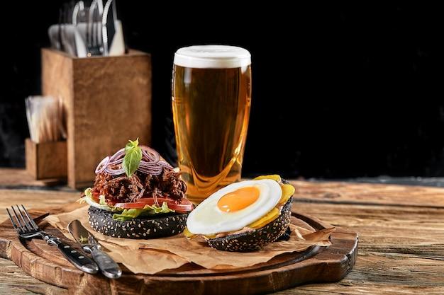 Hamburger mit ei und bier. ein standardsortiment an getränken und speisen in der kneipe, bier und snacks. dunkler hintergrund, fastfood. traditionelles amerikanisches essen.
