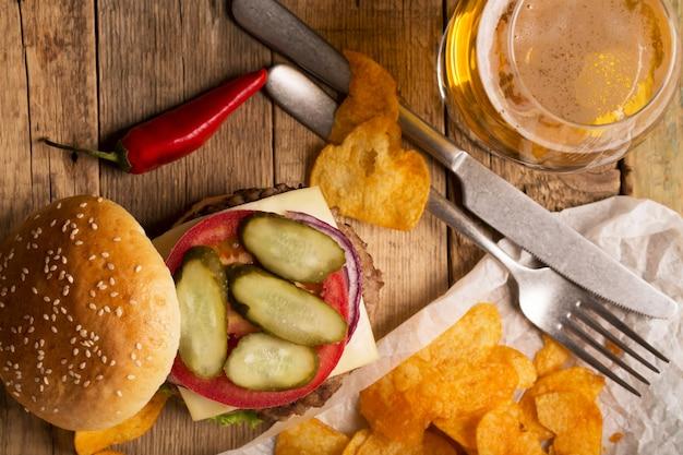 Hamburger mit fleischkotelett. kartoffelchips und bier
