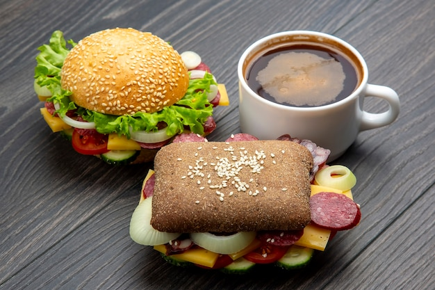 Hamburger mit gemüse und wurst und kaffee auf einem grau