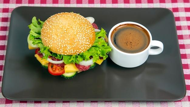 Hamburger mit gemüse und wurst und kaffee auf grauem hintergrund. fast food und frühstück. kalorien und ernährung.
