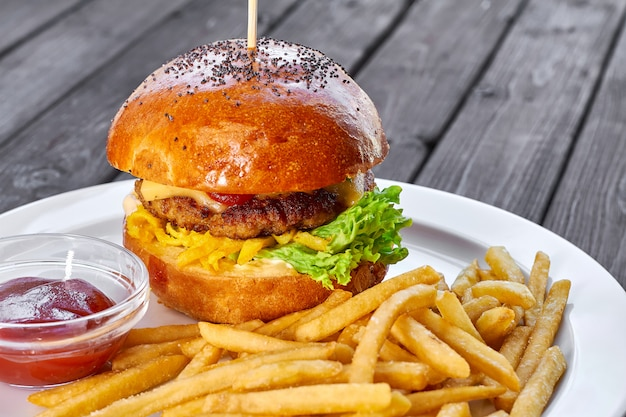 Hamburger mit hühnerschnitzel, käse, pommes frites, tomaten, salat, sauce und ketchup