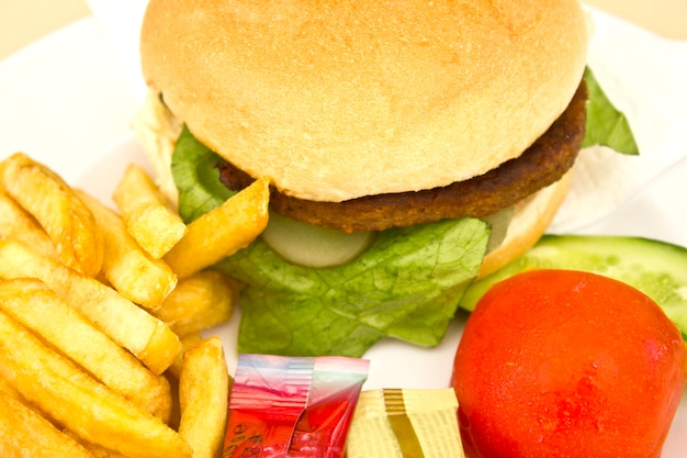 Hamburger mit pommes frites, gurkenscheiben und tomaten