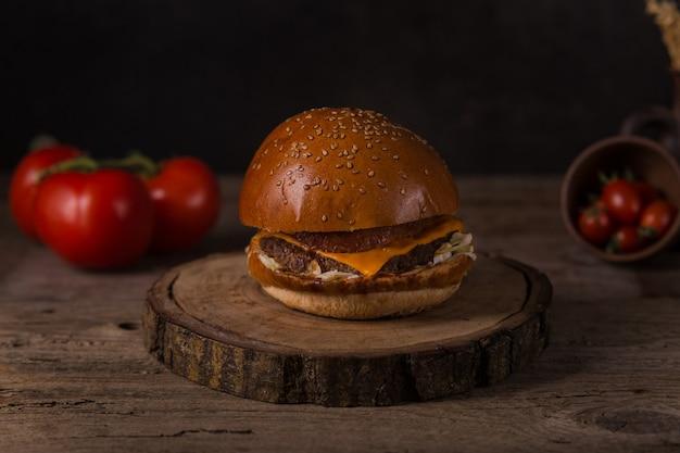 Hamburger mit pommes frites, ketchup, senf und frischem gemüse auf einem holzbrett.
