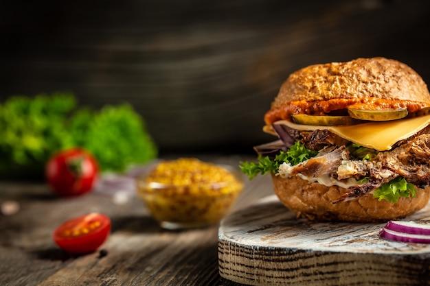 Hamburger mit rindfleisch, käse und gemüse auf rustikalem tisch