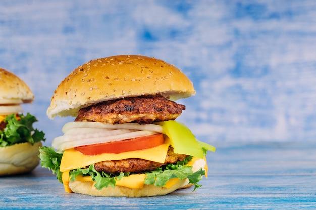 Hamburger mit rindfleisch, käse, zwiebeln und tomaten.