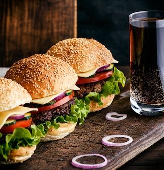 Hamburger mit rindfleisch, zwiebel, tomate, kopfsalat, käse und getränk
