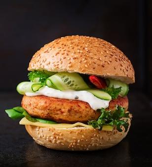Hamburger mit saftigem chicken burger, käse, gurke, chili und tartarsauce auf schwarzem tisch