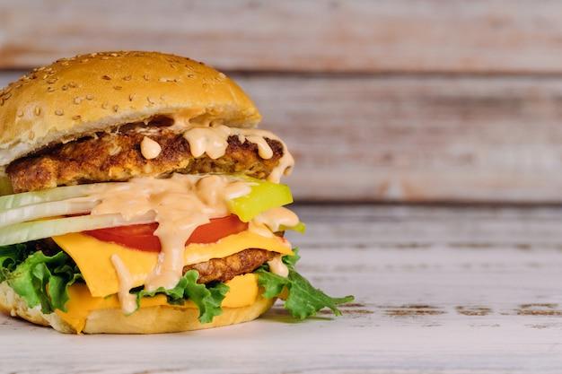 Hamburger mit salat, fleisch, geschmolzener käsesoße.