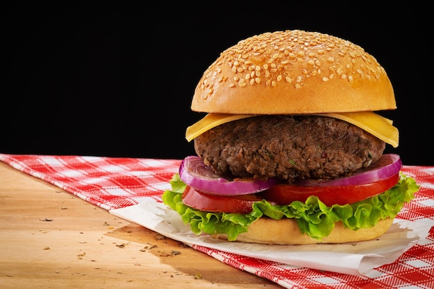Hamburger mit salat, tomaten, roten zwiebeln und käse. holzsockel mit rot kariertem stoff. schwarzer hintergrund und platz für text.