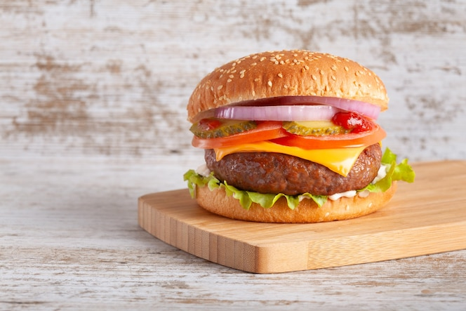 Hamburger mit tomaten, käse, zwiebeln, salat und gewürzgurke auf holzbrett