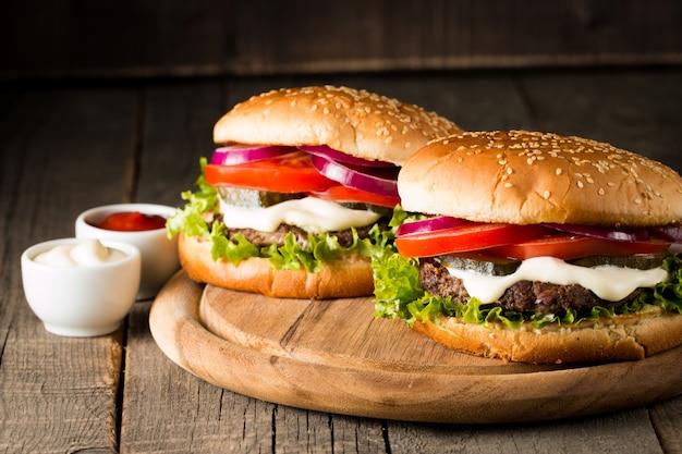 Hamburger mit tomaten, rindfleisch und soße.