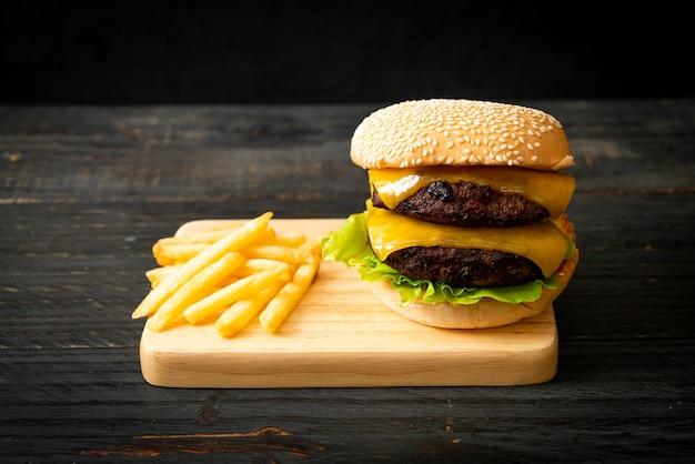 Hamburger oder beef burger mit käse und pommes frites - ungesunde ernährungsweise