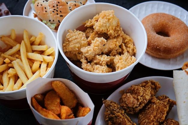 Hamburger, pommes frites, donut, nuggets und schokolade auf schwarz