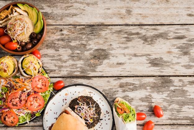 Hamburger; salat; burritoverpackung und -schüssel mit kirschtomaten auf hölzernem strukturiertem hintergrund