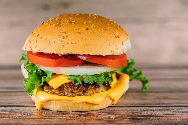 Hamburger sandwich mit geschmolzenem käse, tomate, fleisch.