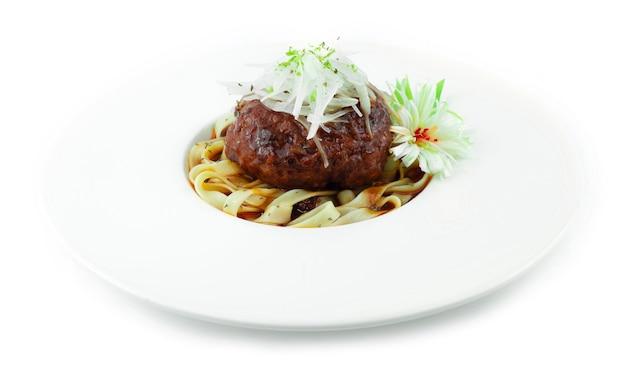 Hamburger steak (hambagu) mit pasta auf zwiebelscheiben japanisches essen fusion stil dekoration geschnitzte lauch bündel zwiebel seitenansicht