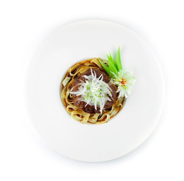 Hamburger steak (hambagu) mit pasta ontop scheibenzwiebel japanisches essen fusion stil dekoration geschnitzte lauch bündel zwiebel draufsicht