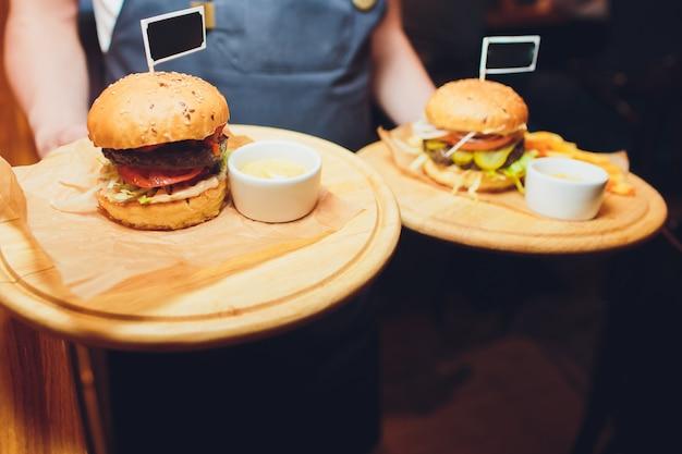 Hamburger und pommes auf dem holztablett.