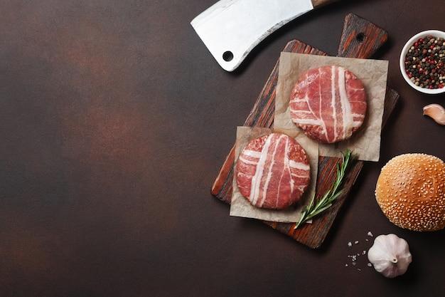 Hamburger zutaten rohe koteletts, salat, brötchen und zwiebeln auf rostigem hintergrund. draufsicht mit platz für ihren text.
