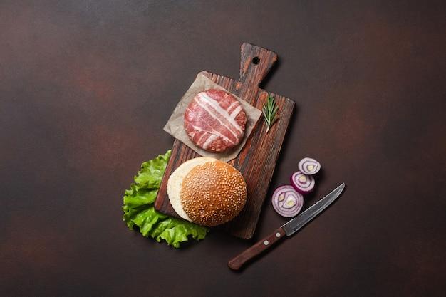 Hamburger zutaten rohes schnitzel, tomaten, salat, brötchen, käse, gurken und zwiebeln