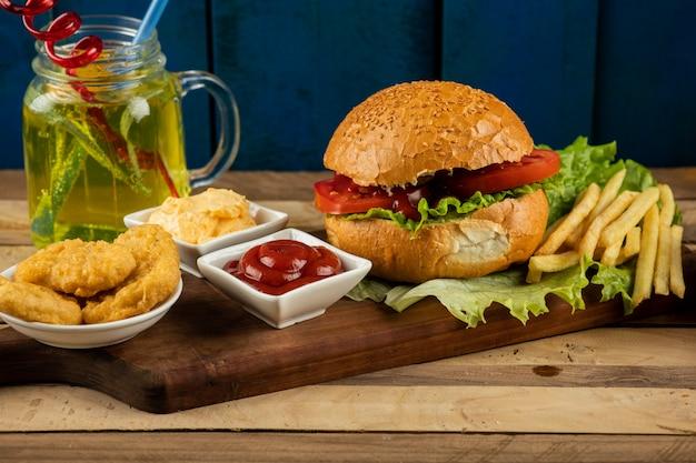 Hamburger, zwiebelröllchen und bratkartoffeln mit saucen und tomaten, serviert mit einem glas saft
