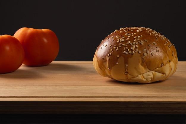 Hamburgerbrot und tomaten. holzbasis und schwarzer hintergrund.