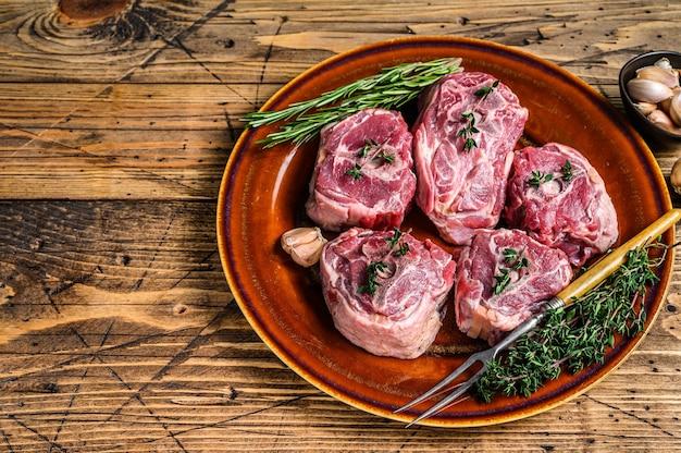 Hammelfleisch lammhalsfleisch auf einem rustikalen teller mit thymian und rosmarin