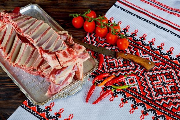 Hammelfleisch mit gewürzen, zwiebeln aus rotem pfeffer und knoblauch auf schiefer und holztisch.