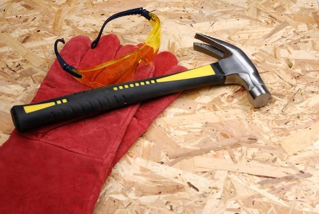 Hammer, brille und handschuhe auf sperrholz