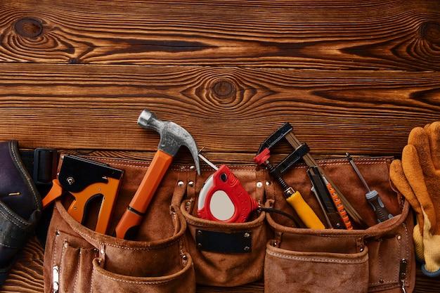 Hammer, hefter und schraubendreher, maßband und bügelsäge in ledertasche auf holztisch. professionelles instrument, tischlerausrüstung, befestigungs-, gewindeschneid- und schraubwerkzeuge