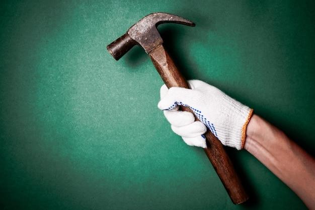 Hammer in der hand mit schutzhandschuh auf grünem hintergrund. freier platz für text